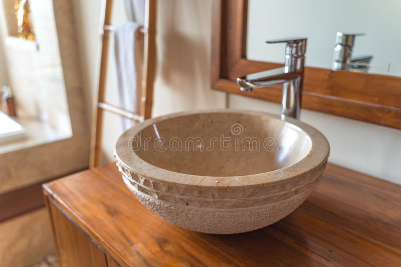 Crafted hand washing sink made of stone in a luxury hotel bathroom stock image