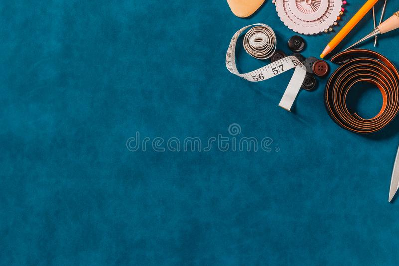 Crafting tools on natural leather on background. Frame with sewing tools and accessories. Top view royalty free stock photo