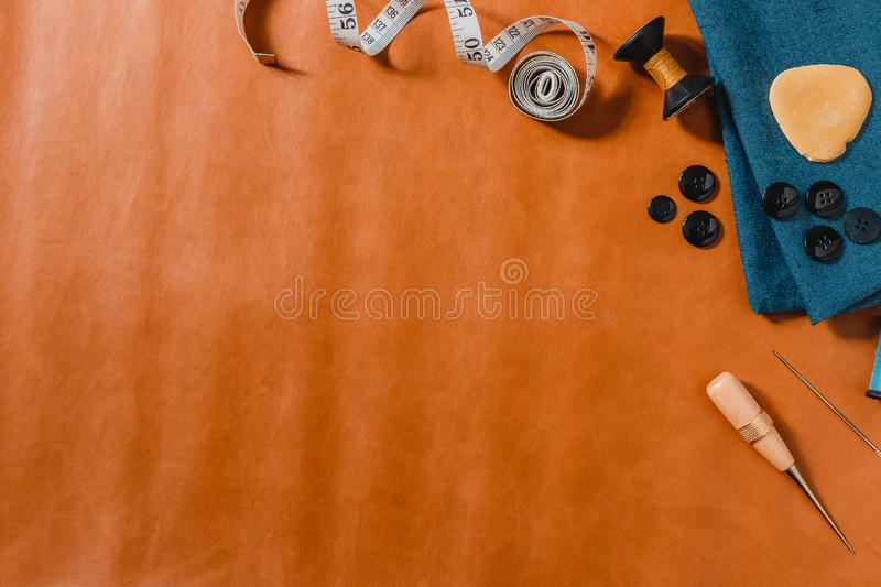 Crafting tools on natural leather on background. Frame with sewing tools and accessories.Top view royalty free stock image