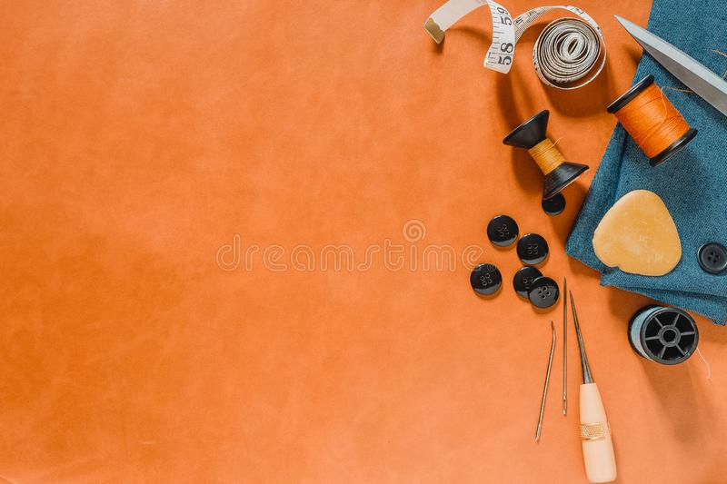 Crafting tools on natural leather on background. Frame with sewing tools and accessories.Top view royalty free stock photo