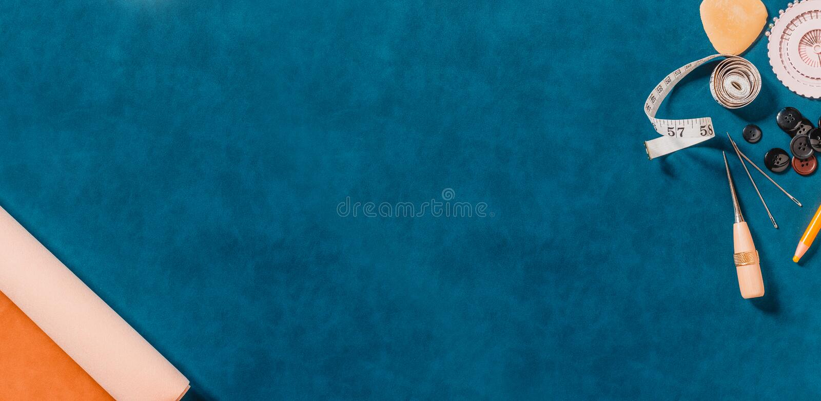 Crafting tools on natural leather on background. Wide frame with sewing tools and accessories. Top view royalty free stock photo