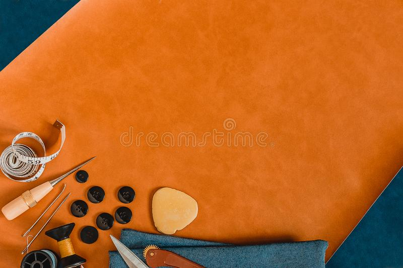 Crafting tools on on natural leather 2 color background. Frame with sewing tools and accessories. Top view royalty free stock photos
