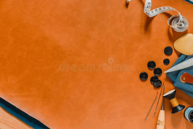 Crafting tools on natural leather 2 color and wooden table background. Frame with sewing tools and accessories. Top view stock photos