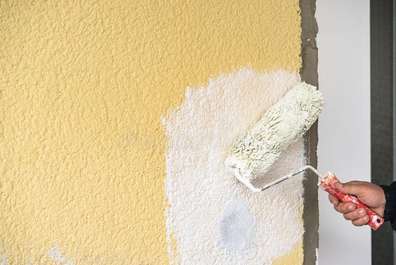 Manual worker is painting wall with painter roller royalty free stock photography