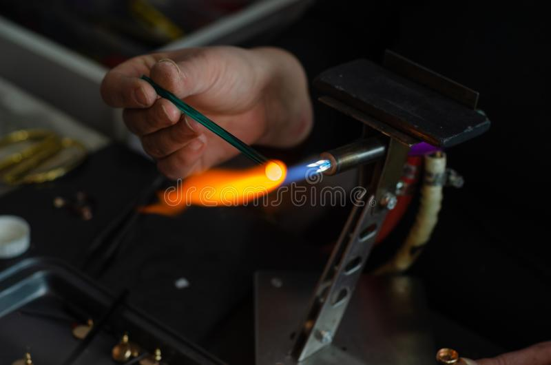 Craftsman is making  a product made of glass. The craftman woman is holding  of a flame and melting glass piece on dark background stock photo