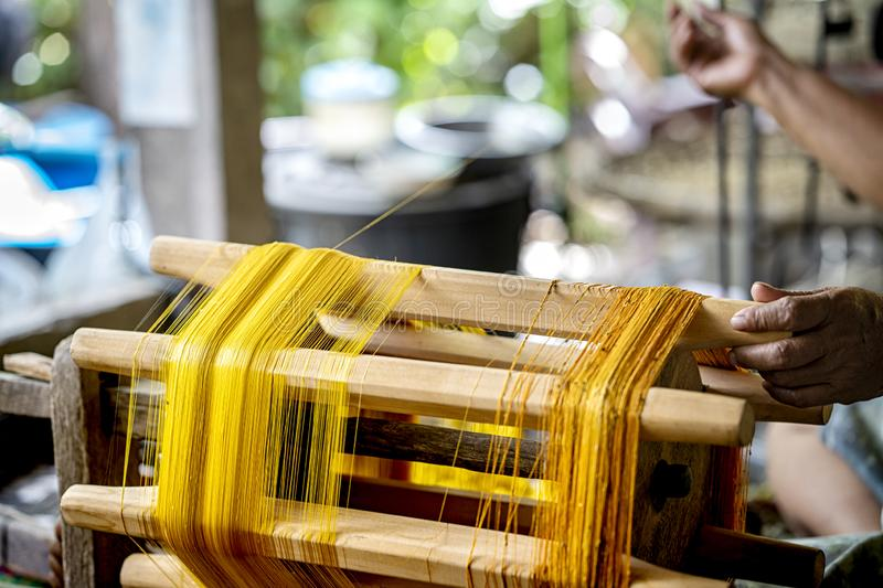 Crafts and craftsmanship. Silk raising for silk threads. yarn warping machine in a textile weaving crafsmanship. Hand of woman royalty free stock photography