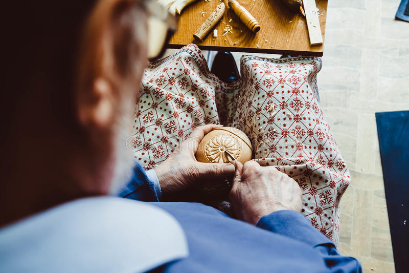 A craftsman carves wood. The hands of the craftsmen carved wooden product royalty free stock image