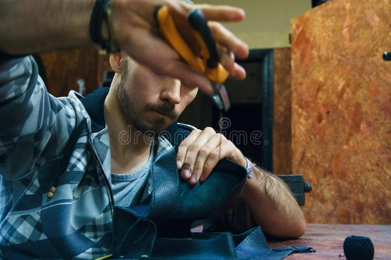 Craftsman creates leather bag in workshop stock photography