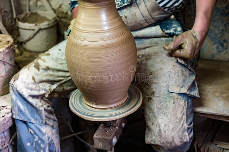 Craftsman in dirty clothes molding clay into desired shape on potter`s wheel royalty free stock image