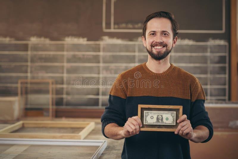 Craftsman entrepreneur proudly displaying a framed bank note stock images