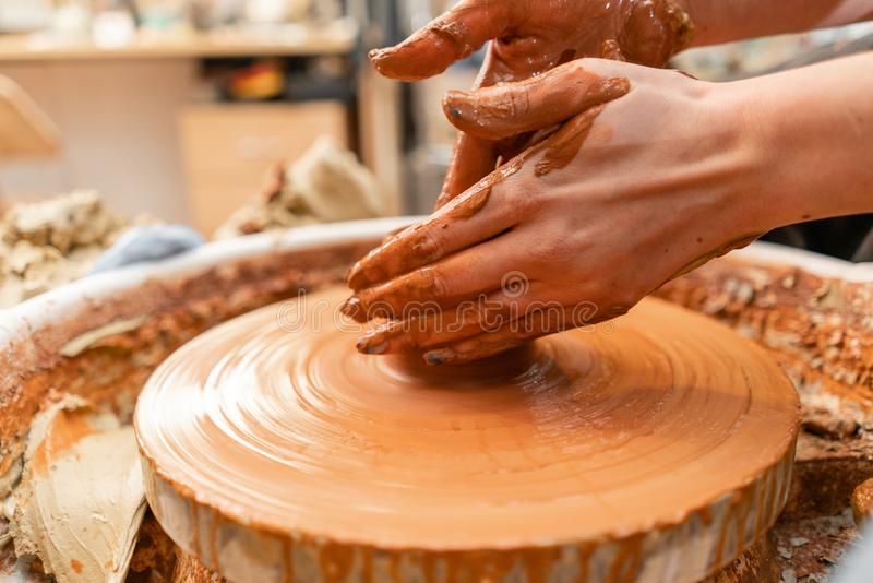 Craftsman hands making pottery bowl. Woman working on potter wheel . Family business shop sculpts pot from clay view top. Happy woman working on potter wheel in stock image