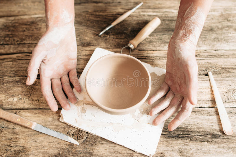 Craftsman hands with pottery and tools on wood royalty free stock photos