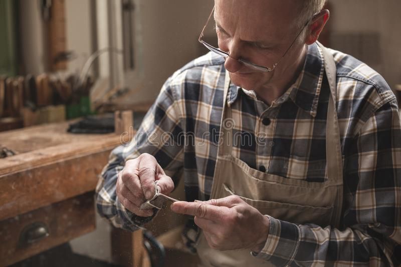 Craftsman highly focused working inside a workshop. Mature artisan in a workshop sanding down a violin bow manually royalty free stock image