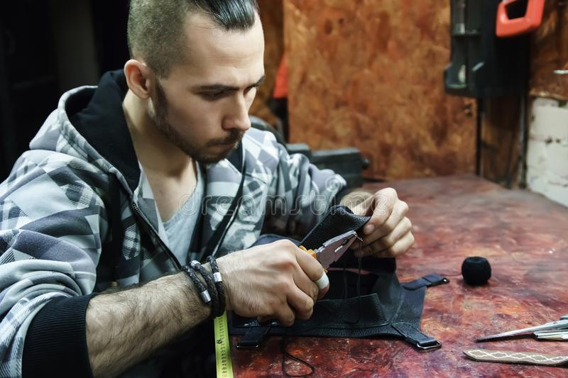 Tanner creating leather bag in workshop. royalty free stock photography