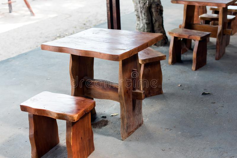 Small handmade table. Craftsman made small wooden table and two matching stools (buffets) outdoors for restaurant (diners) users royalty free stock photography