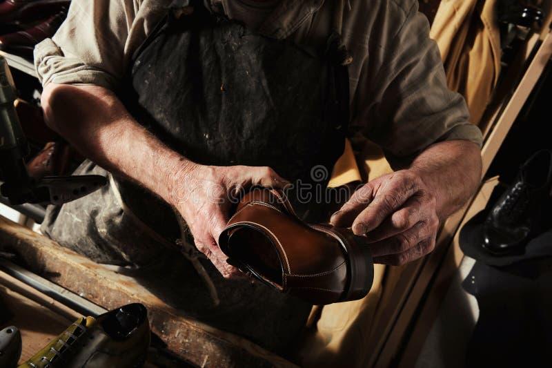 Craftsman making luxury handmade man shoes royalty free stock images