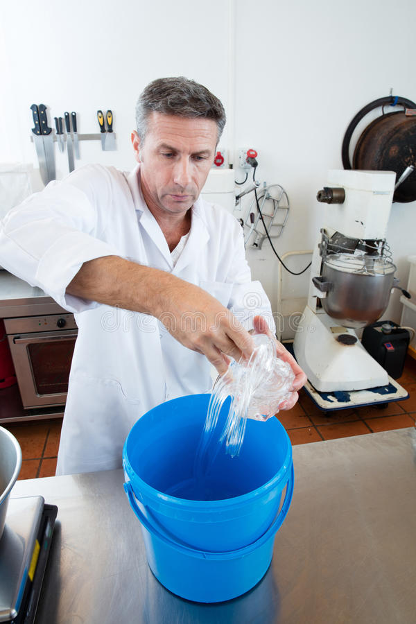 Craftsman preparation of glucose for French sweet nougat specialty. Preparation of dose of glucose for French sweet nougat specialty by male craftsman, scaling stock photos