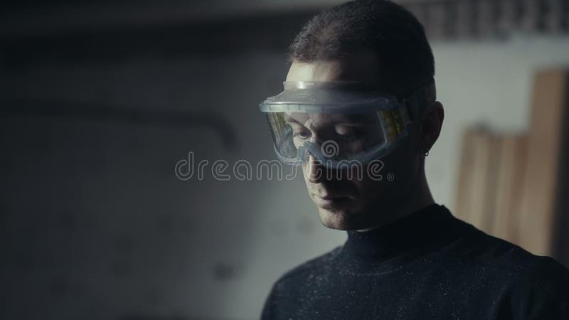 Craftsman with saved glasses at workstation. Man in a protective mask royalty free stock photography