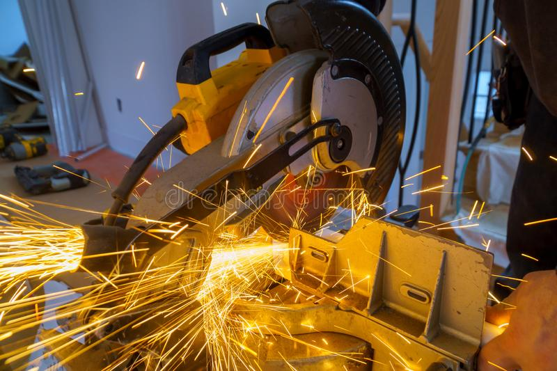 Craftsman sawing metal with disk grinder in workshop. Craftsman sawing metal with disk grinder in sparks while grinding iron cutting blade circular industrial royalty free stock photo