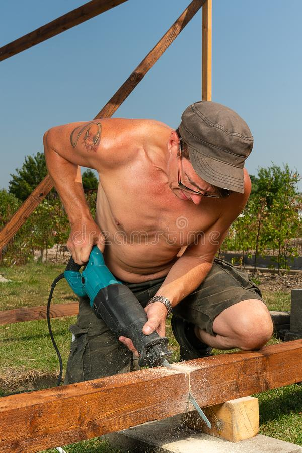 Craftsman saws through a beam with an electric saw royalty free stock image