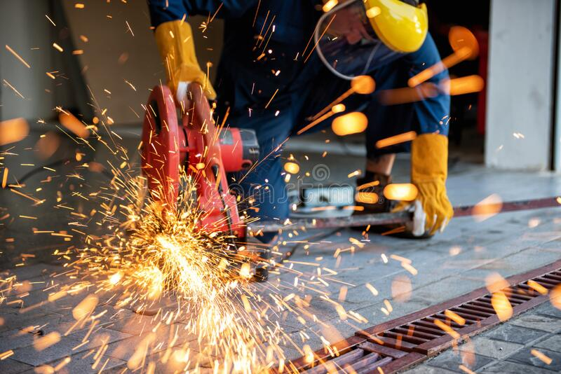 Craftsman Welding is Cutting Steel Work, Welder Man in Safety Protective Equipment Doing Metalwork in Construction Site. Engineering Labor Skill and Workshop royalty free stock images