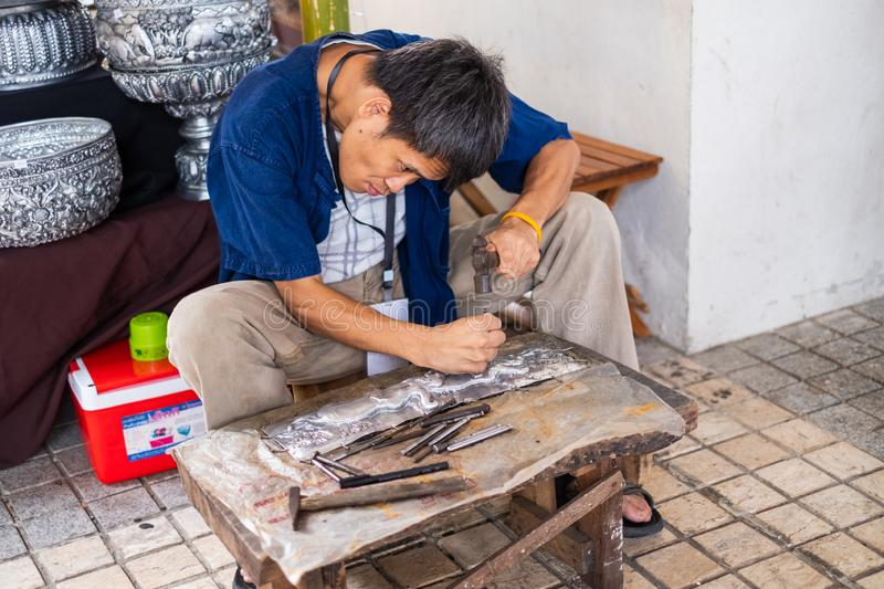 Craftsman working on a crave on silver plate. Chiang Mai ; THAILAND - June 29 , 2019 Craftsman working on a crave on silver plate stock photo