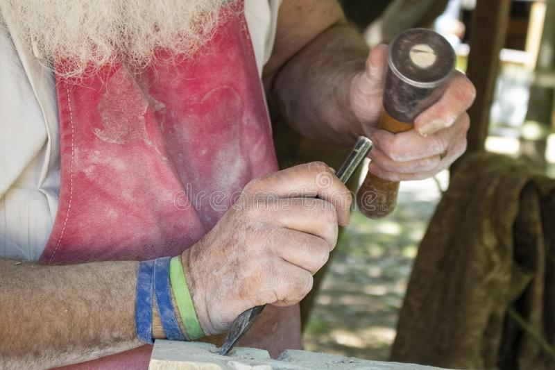 Craftsmans händer genom att använda stämjärnet och klubban för att snida stenen royaltyfri fotografi