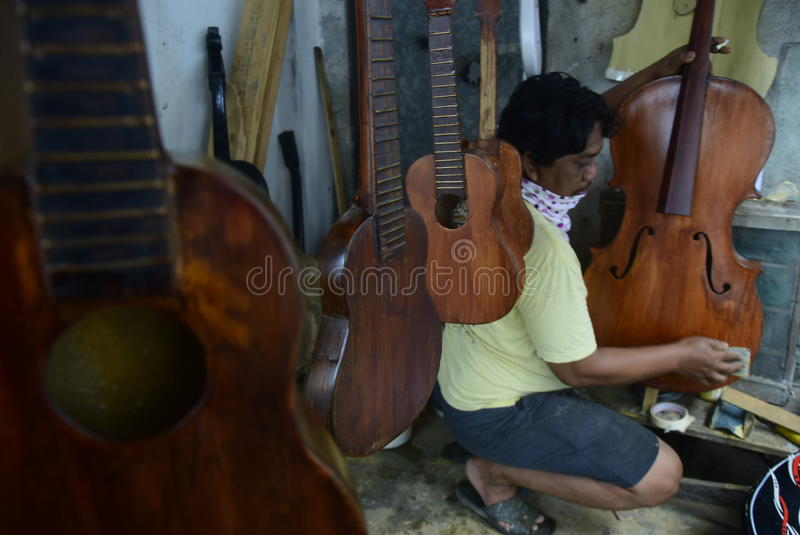CRAFTSMEN stringed SEMARANG. Craftsmen stringed instruments such as the guitar, violin and bass busy making framework guitar instrument in Pusponjolo, Semarang stock photography