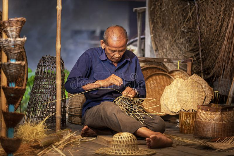 Craftsmen of Thai. An old man who is the craftsmanship in Buriram Province Weaving a basket of bamboo. Craftsmanship that has been. Carried on since ancient royalty free stock photography