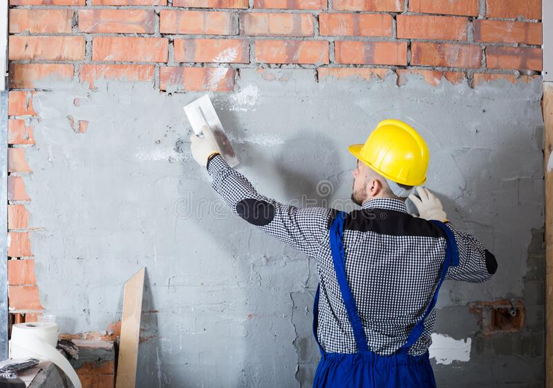 Craftsperson is plastering the wall. At the closet stock photos