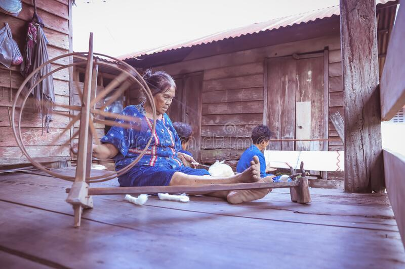 Craftsperson working. Old woman process homespun cotton cloth weaving in the community. Senior women spinning natural cotton. Craftsperson working. Old women stock photos
