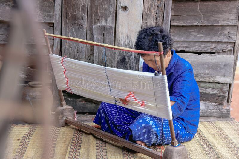 Craftsperson working. Old woman process homespun cotton fabric weaving in community. Senior women create fabric pattern form. Craftsperson working. Old woman stock photos