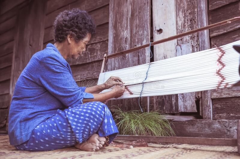 Craftsperson working. Old woman process homespun cotton fabric weaving in community. Senior women create fabric pattern form. Cotton threads or yarn royalty free stock image