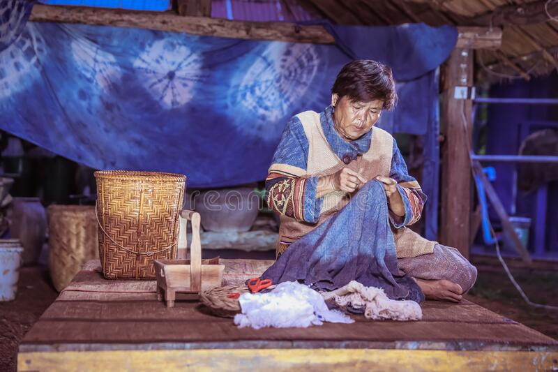 Craftsperson working. Old woman sewing homespun cotton cloth in community. Senior women use a sewing needle. Old woman tailoring. Craftsperson working. Old stock photography