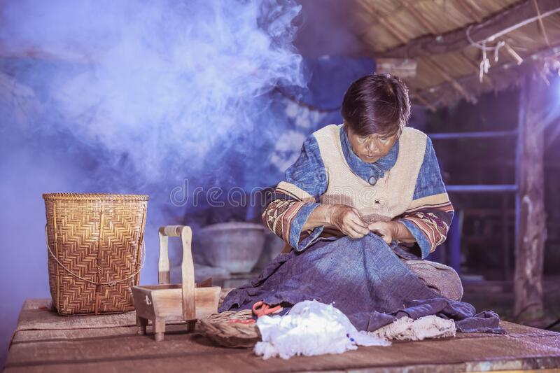 Craftsperson working. Old woman sewing homespun cotton cloth in community. Senior women use a sewing needle. Old woman tailoring. Tailor working stock photos
