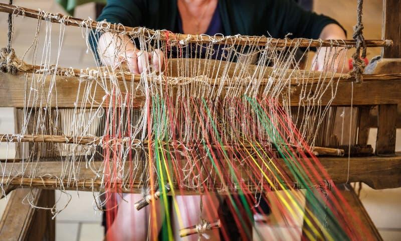 Craftspersonvrouw die achter een oud houten weefgetouw werken stock foto's