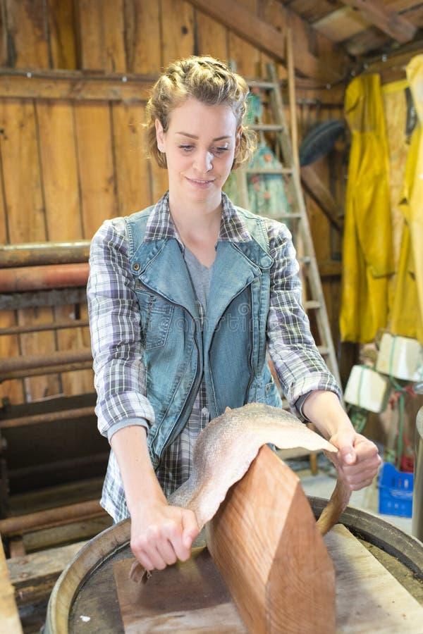 Craftswoman που λειτουργεί στο δέρμα φιδιών στο εργαστήριο στοκ φωτογραφίες
