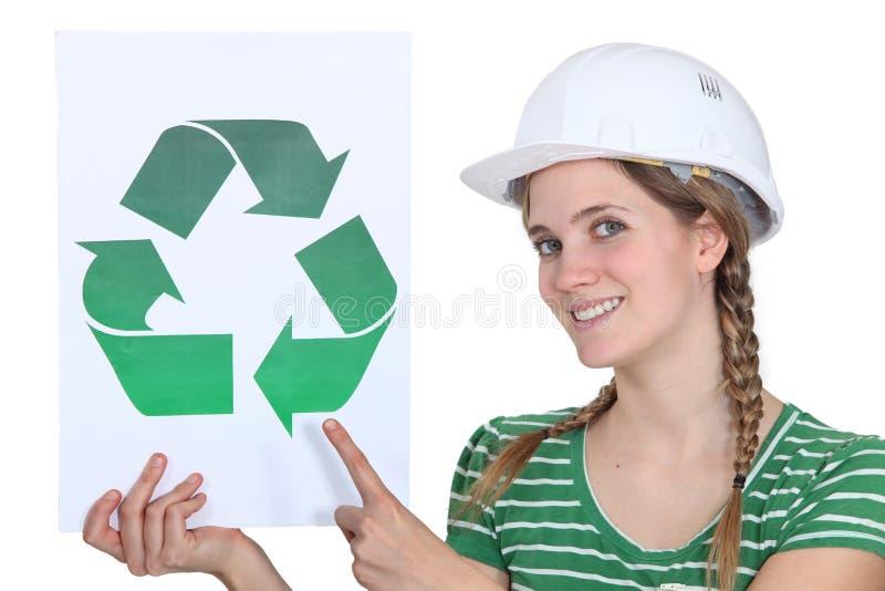 Craftswoman που παρουσιάζει το σημάδι ανακύκλωσης στοκ εικόνα με δικαίωμα ελεύθερης χρήσης