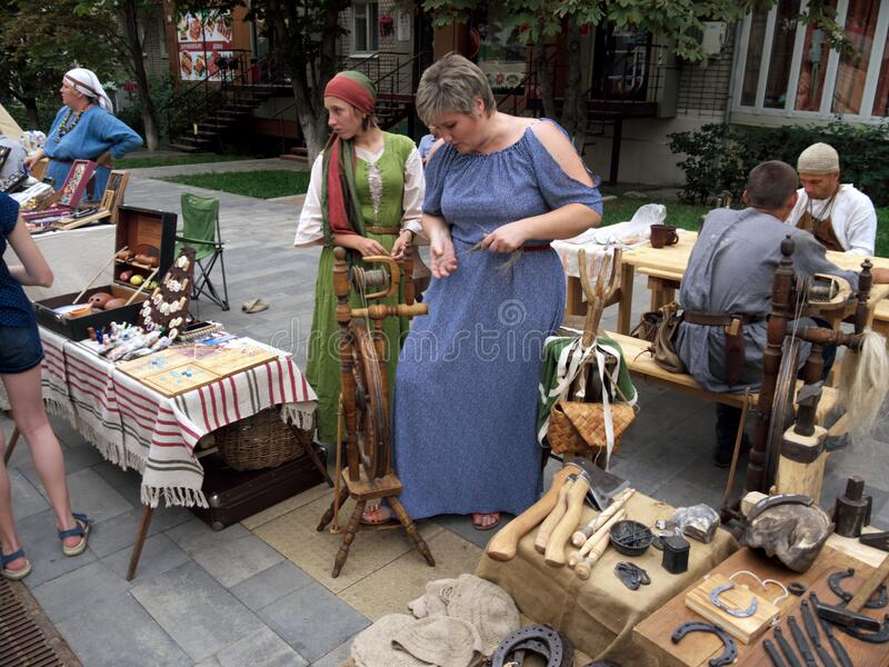 The craftswoman gives a lesson to a passerby woman how to spin yarn in ancient times. royalty free stock photography