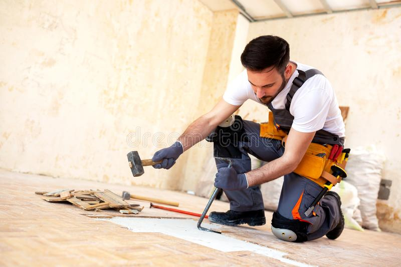 Crafty handyman removing old parquet stock photography