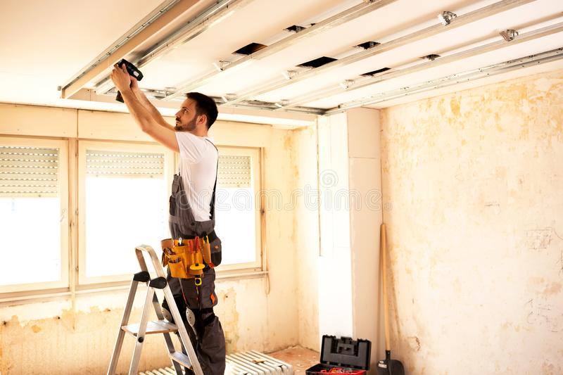 Crafty worker arranging ceiling construction stock photos