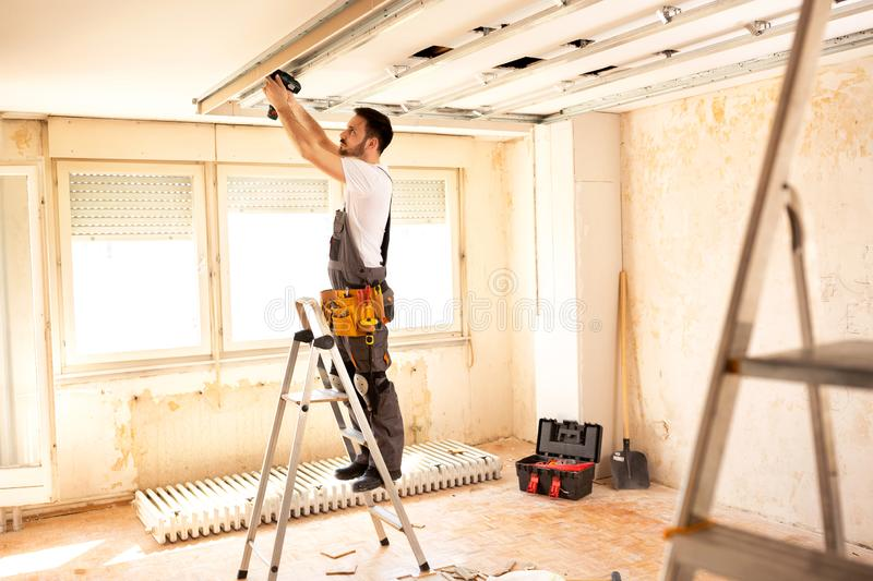 Crafty worker arranging ceiling construction stock photography