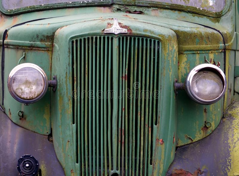 Close up of the front of an old abandoned rusting green truck covered in moss stock photos