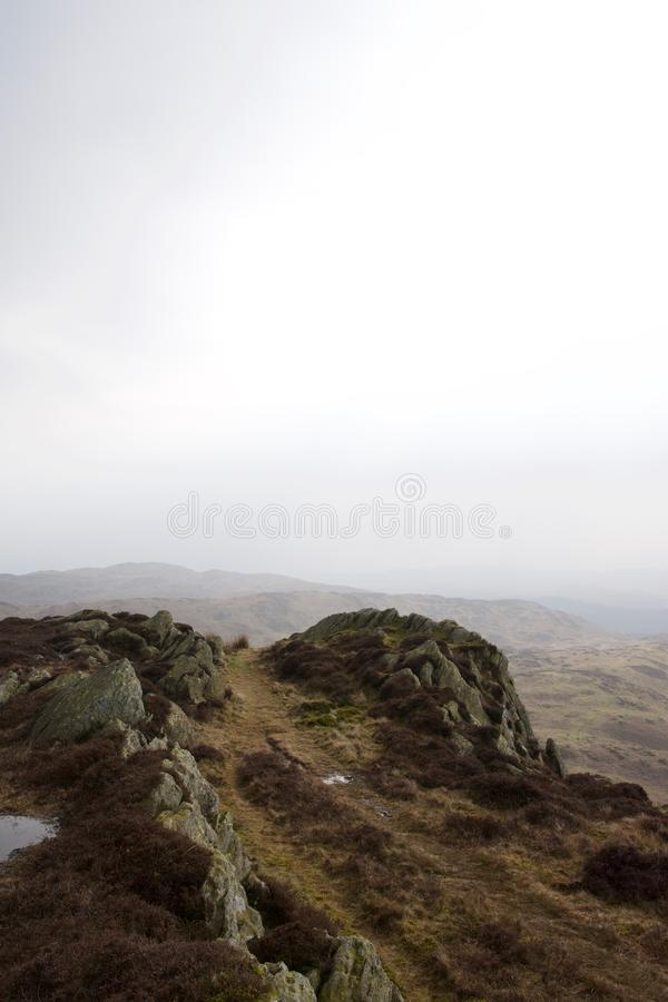 Craggy rocky moorland with misty hills. Heather and bracken moorland typical of the north of England and Scotland, specifically in the Lake District, Cumbria stock photography
