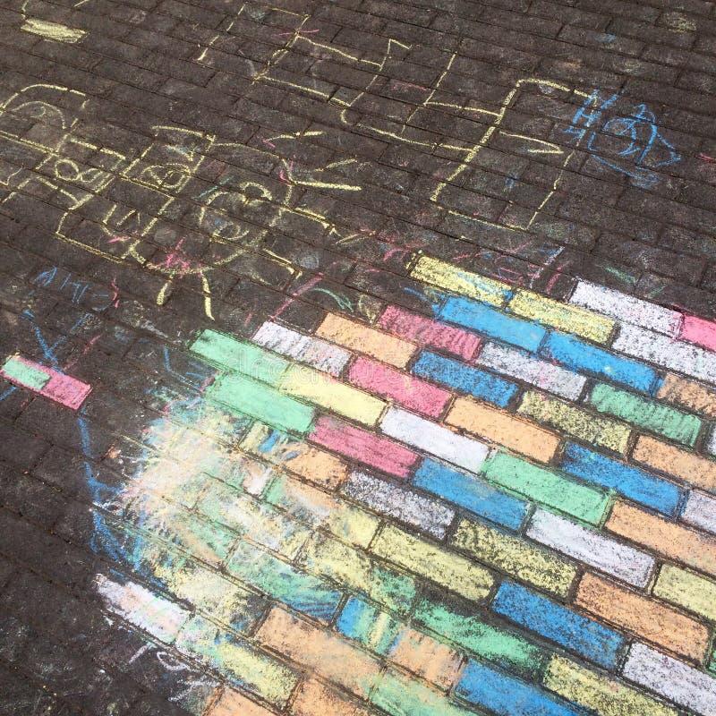 Craie colorée des pavés et du dessin de crayon créés par des enfants avec des couleurs en pastel photographie stock