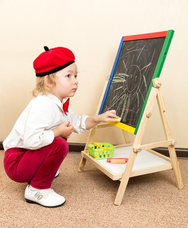 Craie de dessin mignonne de fille d'enfant sur le chevalet dans le costume de l'artiste dans le jardin d'enfants photo libre de droits