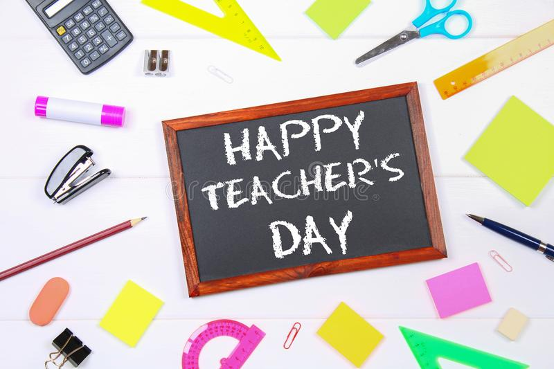 Craie des textes sur un tableau : Jour heureux du ` s de professeur Fournitures scolaires, bureau, livres, pomme photos stock