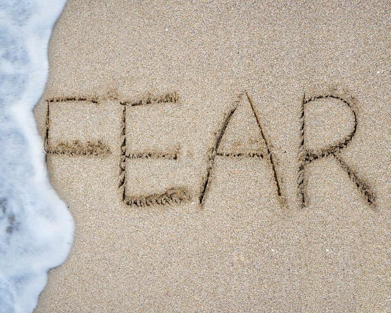 Craignez la main de mot écrite avec la mousse de vague sur la plage de sable image libre de droits