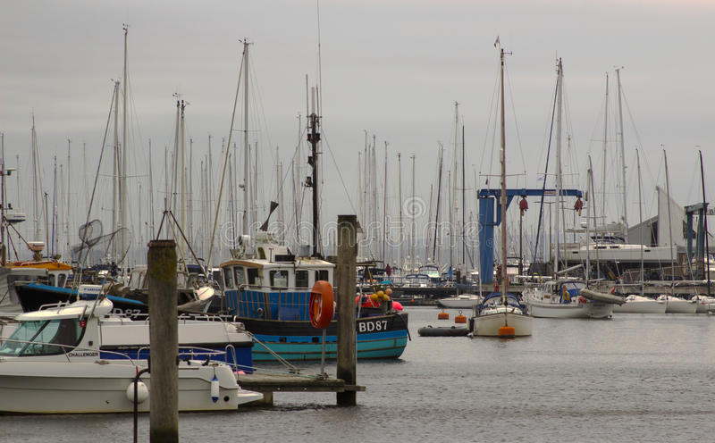 The crammed marina at Lymington Harbour home to the Royal Lymington Yacht Club. Taken on a dull grey summer's day in June. The crammed marina at Lymington stock images