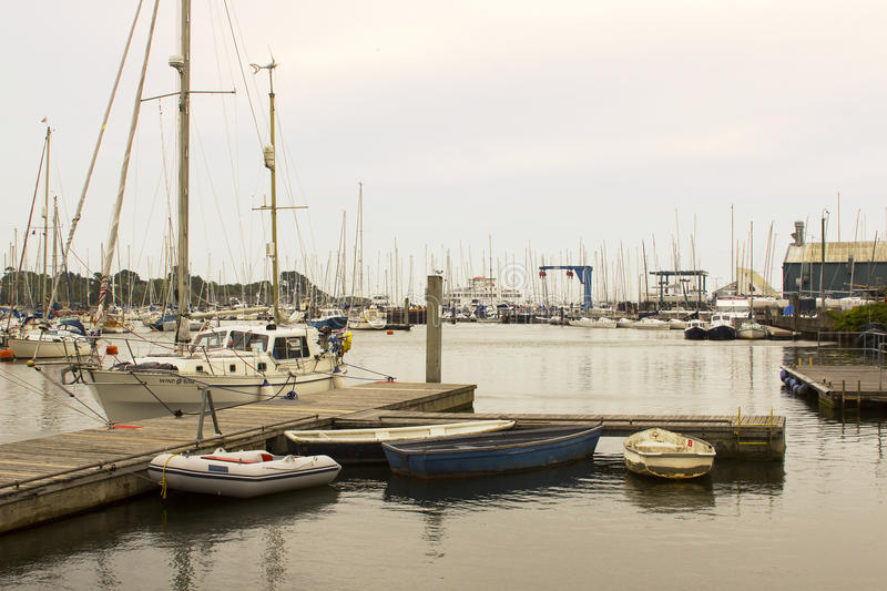 The crammed marina at Lymington Harbour home to the Royal Lymington Yacht Club. Taken on a dull grey summer`s day in June. The crammed marina at Lymington stock image